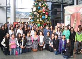Students in front of a decorated Christmas tree